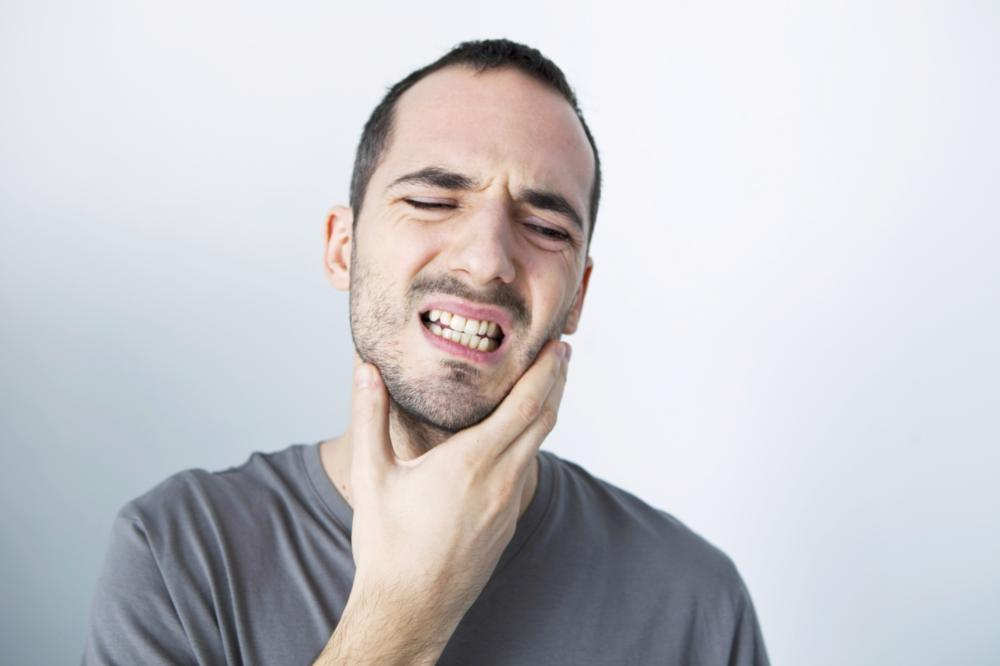 Man holding jaw from pain