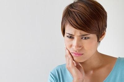 Woman holding jaw from toothache before root canal
