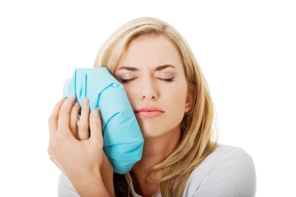 Woman holding ice pack to sore jaw