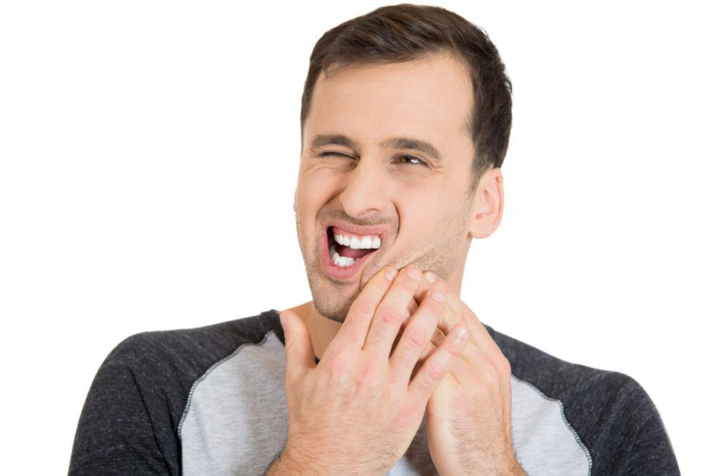 Man holding jaw from pain | Dentist Chesterfield MO