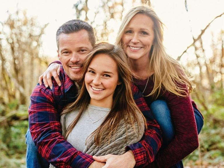 family hugging at park | chesterfield mo dentist