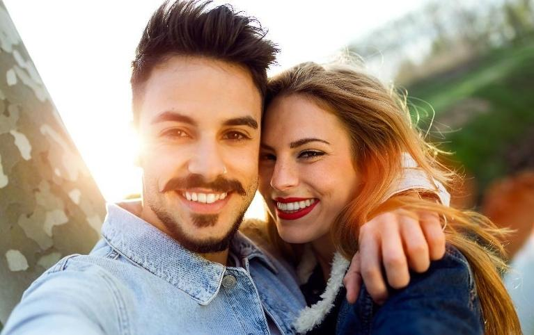 Couple smiling with sun setting behind them